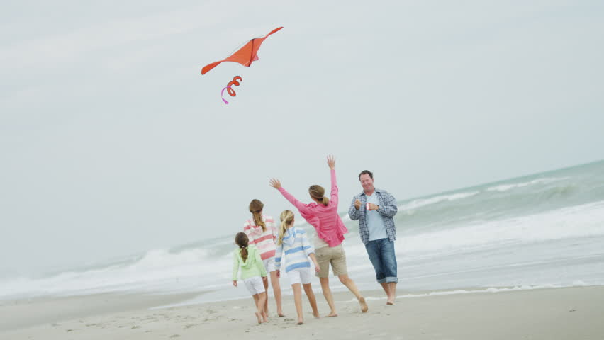 Three pretty young Caucasian sisters having fun beach Fall weekend with parents playing toy kite shot on RED EPIC | Shutterstock HD Video #6787261