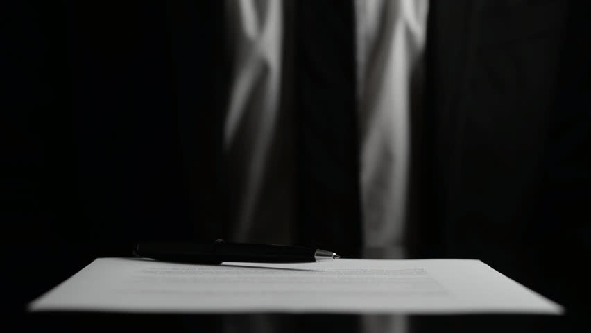 Businessman signing a document or contract with a close up view of his hand with the pen and sheet of notepaper on a desk top. Over black background.