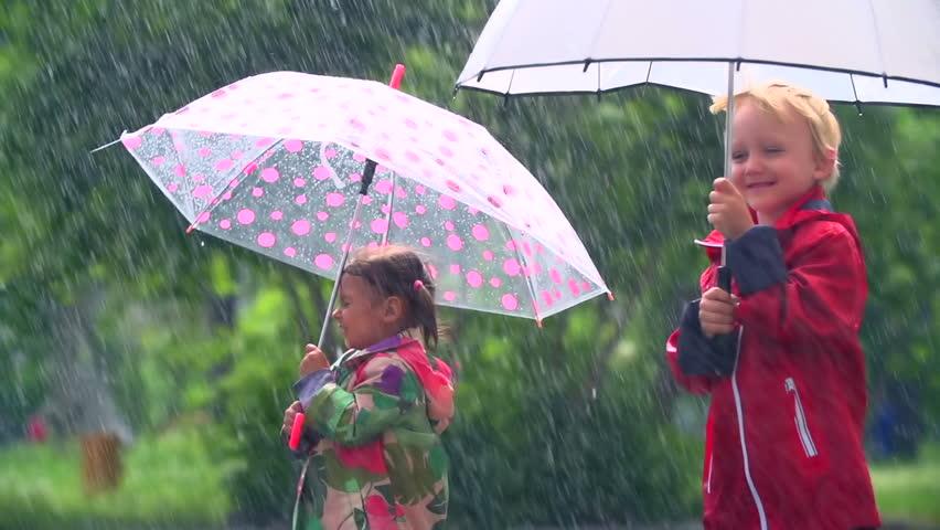 Kids standing under umbrellas in heavy rainfall  - HD stock footage clip