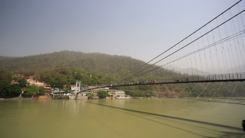 RISHIKESH, INDIA - CIRCA MAY 2014: View of the Ram Jhula bridge. Rishikesh is the world capital of Yoga and the holy city for the Hindus people. - HD stock video clip