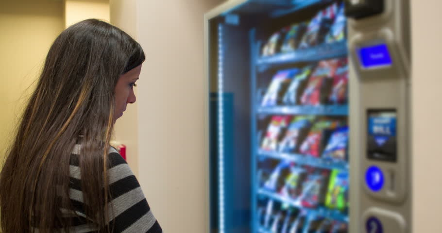 Female looking at snack choices in vending machine 4k