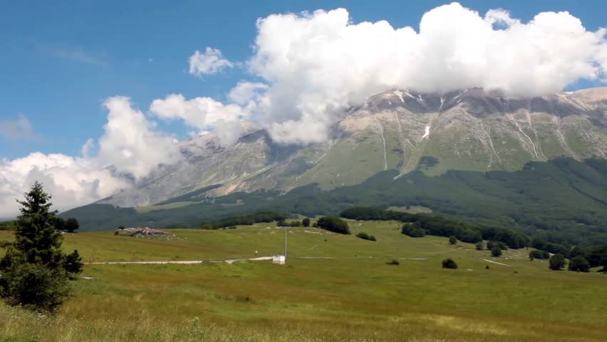 Wide angle shot video of mountain landscape with peaks covered by white clouds, Majella Reserve, Abruzzo, Italy.