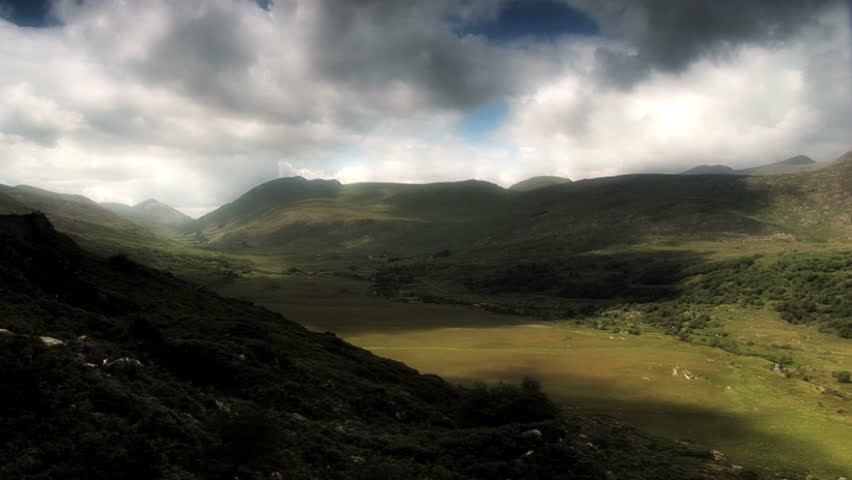 A valley on the west coast of Ireland is bathed in the shadows and streams of sunlight rushing overhead. - HD stock video clip