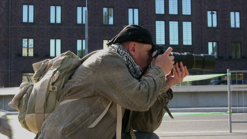 Photographer on the street of the city takes a snapshot of outdoor sports - HD stock video clip