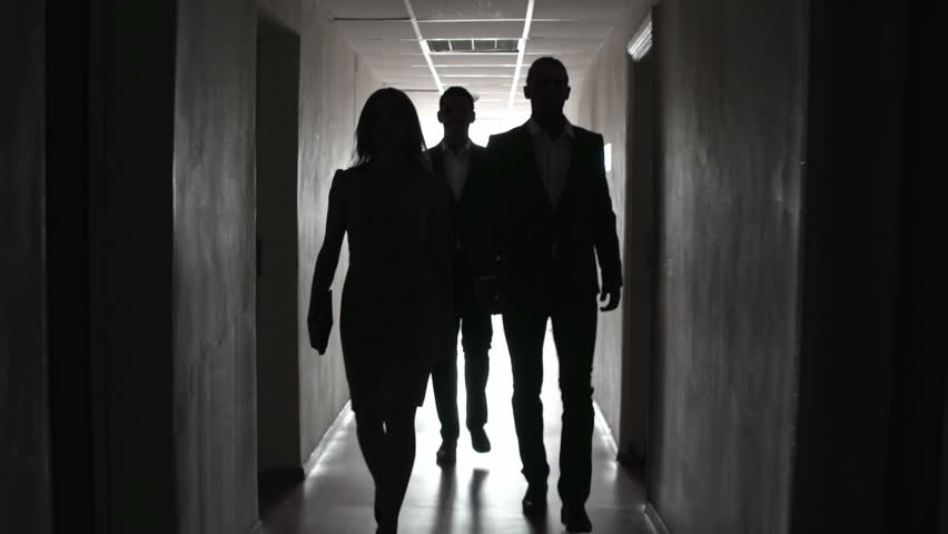 Group of people approaching camera in the dark hallway