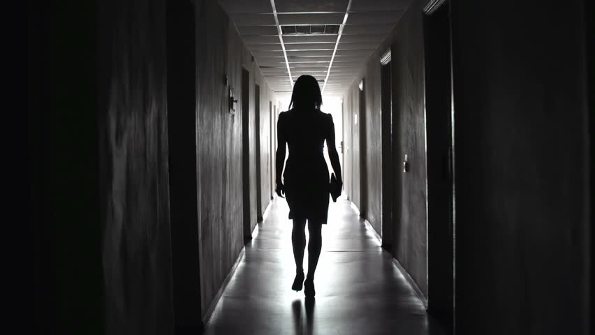 Camera following business-like unrecognizable lady tripping along dark hallway