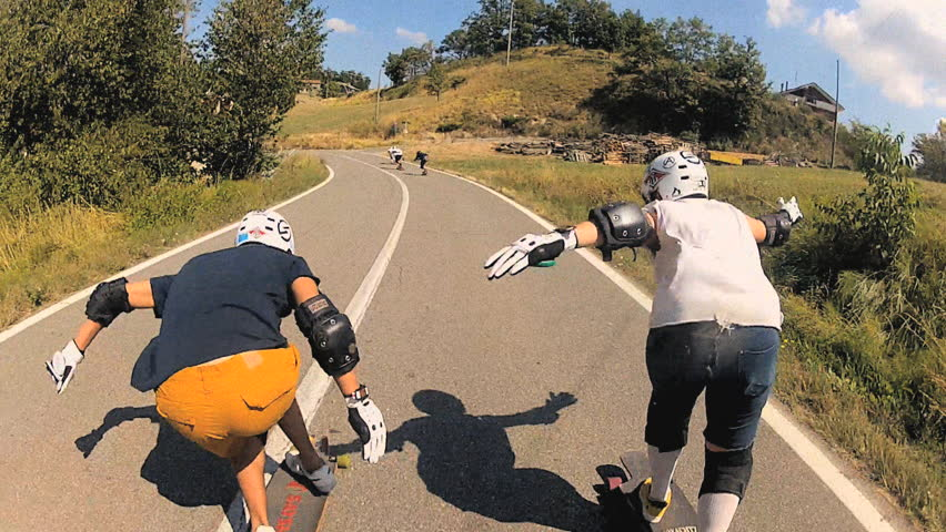 Two longboarders showing tucking techniques and talking to each other while going downhill, various shots