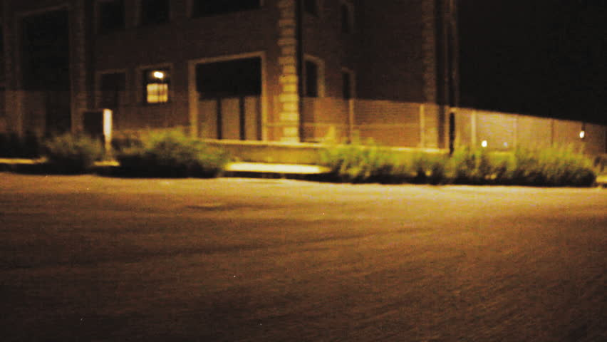 A longboarder while longboarding at night changes his position by sliding, close-up