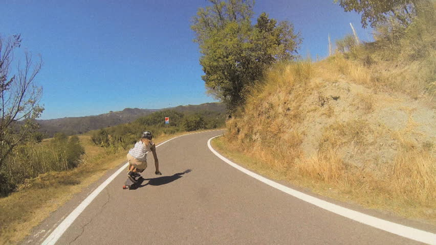 A longboarder performs tucking and sliding techniques while going downhill under a clear blue sky