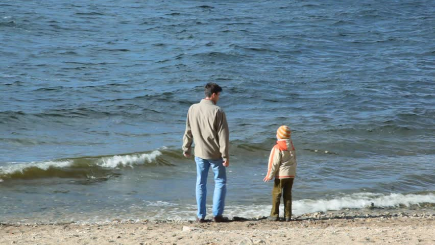 man and boy in sandy coast throws stones at river  - HD stock footage clip