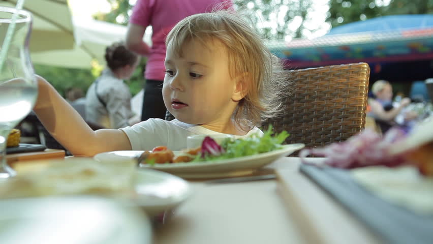 Little cute girl in a cafe eating nuggets | Shutterstock HD Video #6942556