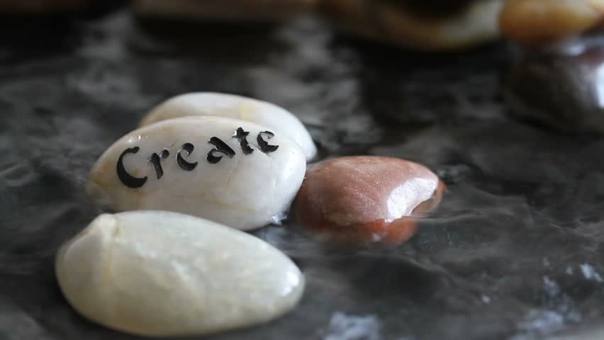 Zen pool with fast running water, closeup of smooth pebble stones and the word create etched into a white stone.