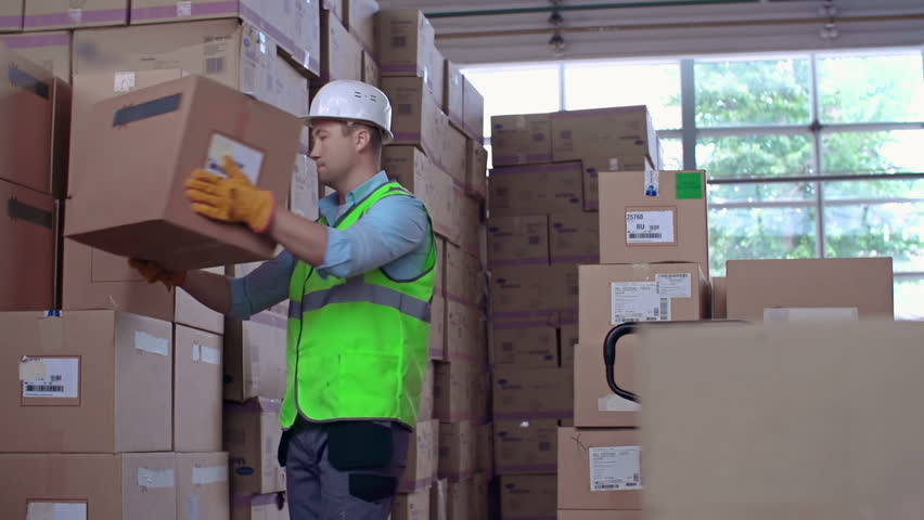 Close up of worker uncarting load and arranging boxes in piles - HD stock footage clip