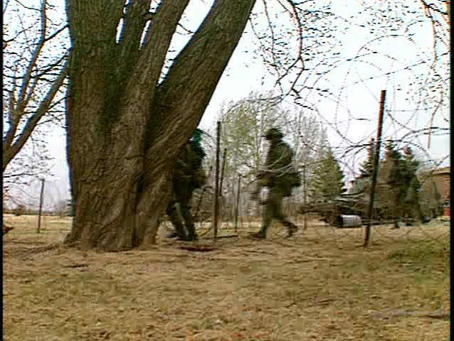 soldiers running through trees assault building. (BetacamSP) - SD stock footage clip