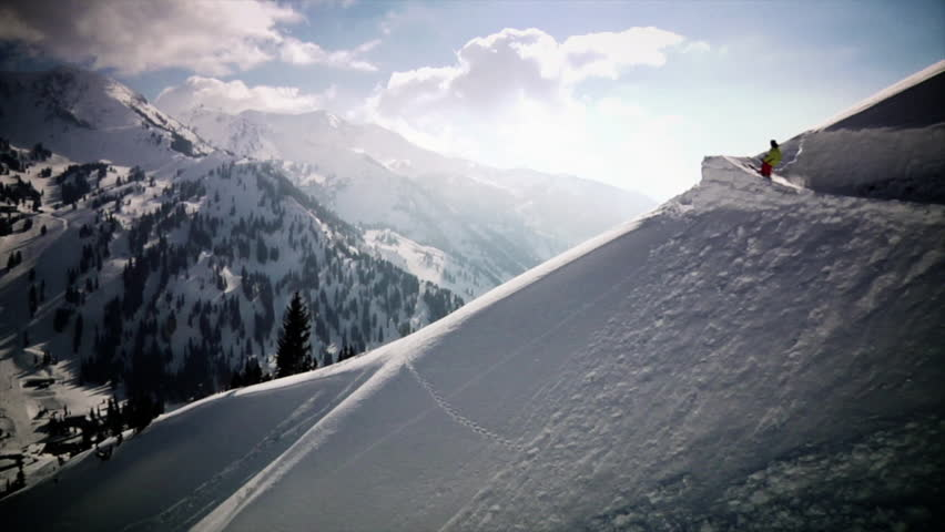 A freestyle skier performs a huge jump over a kicker in slow motion