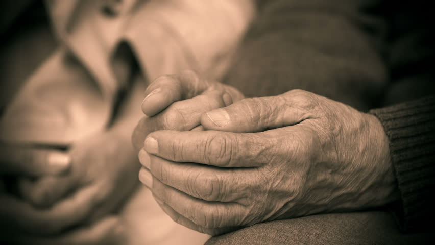 Vintage styled shooting of hand in hand soothing in sepia