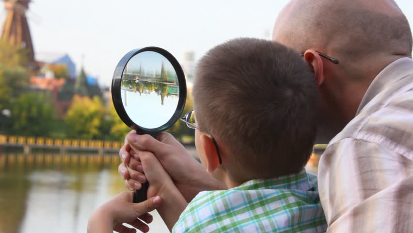 father and son standing on bank of river and looks through magnifying glass  - HD stock video clip