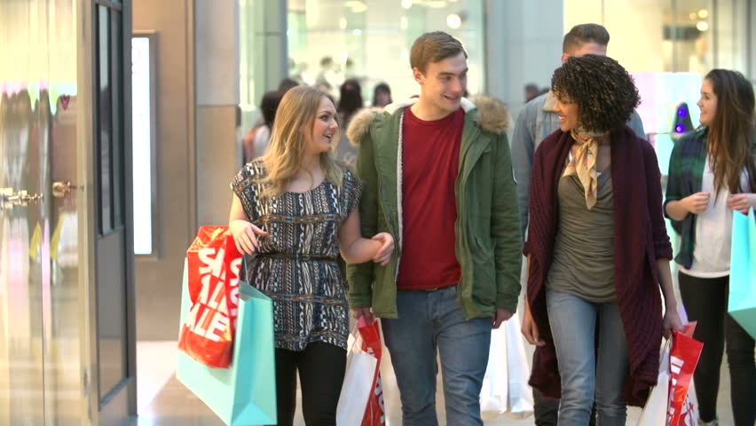 Slow Motion Sequence Of Friends Shopping In Mall Together