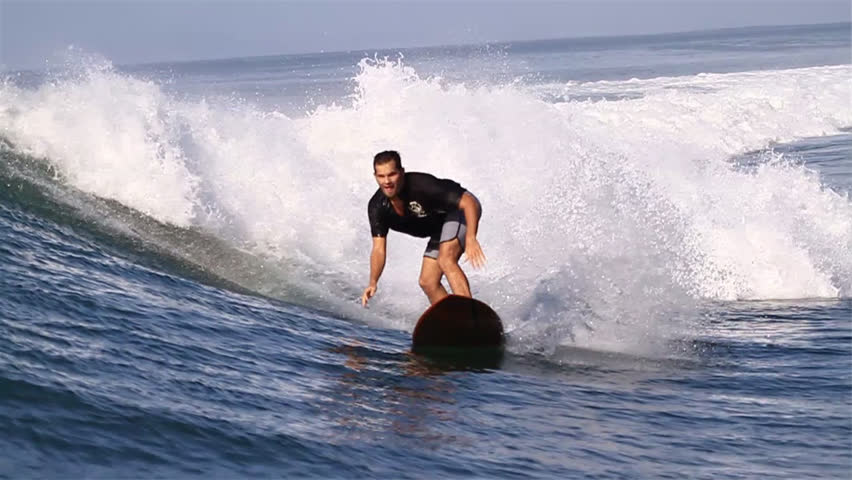 A surfer carves on a wave before coming down with it; a slow-mo shot - HD stock footage clip