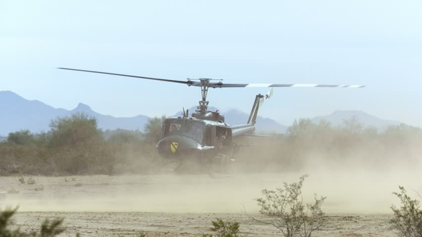 Huey helicopter taking off from the desert, in slow motion - HD stock footage clip