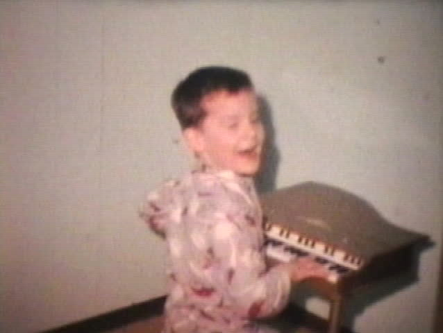 A cute brother and sister play on a cool toy piano while wearing their pajamas.