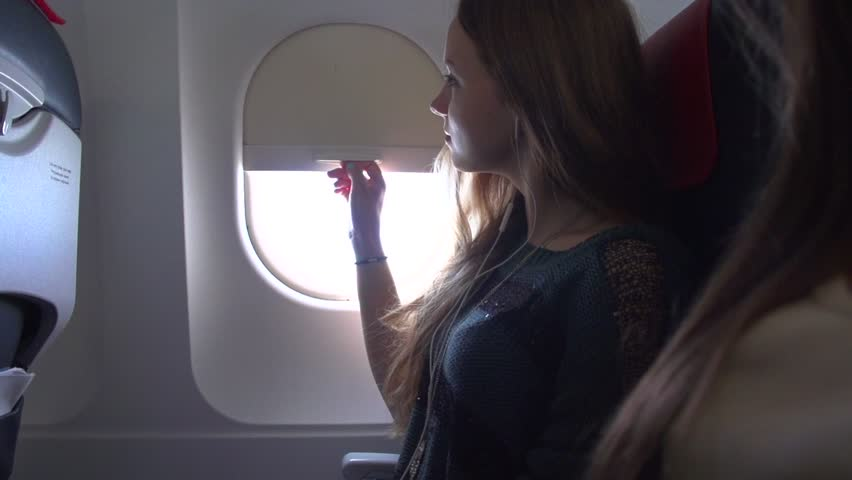 Girl opens an airplane window and  looks out during air travel. Smiling. Happy. Young women traveling by plane together. Tourism concept. Slow motion 240 fps Full HD 1920x1080p. High speed camera shot