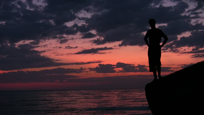 silhouette of young man stands on rock against sunset sky and sea  - HD stock video clip