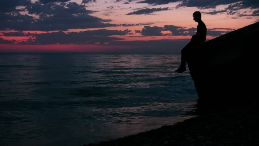 silhouette of teenager sits against sunset sky and throws stones into sea  - HD stock video clip