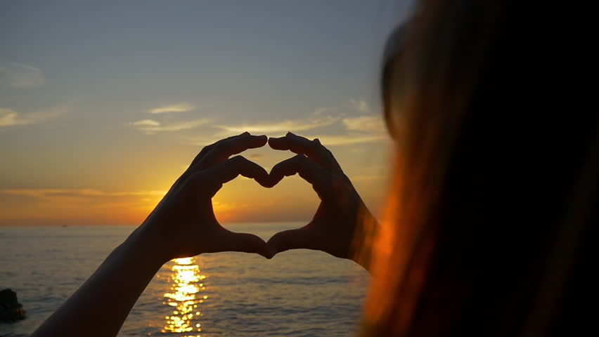SLOW MOTION: Woman looking the ocean sunset through heart hands