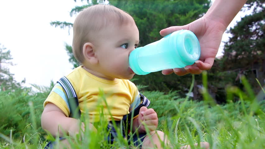 Cute little baby boy drinking water from feeding bottle outdoors | Shutterstock HD Video #7181866