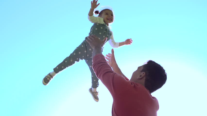 Slow motion of handsome father throwing his adorable daughter in the air - HD stock video clip