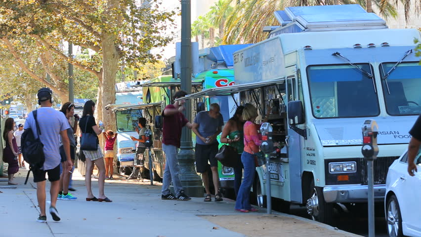 Los Angeles, California - September 5th, 2014: Tourists Purchasing Meals at Food Trucks in Museum Row of Miracle Mile, September 5th, 2014 in Los Angeles, California.