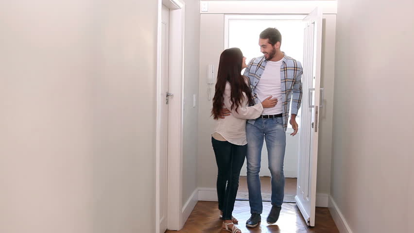Attractive couple opening the front door in their new home