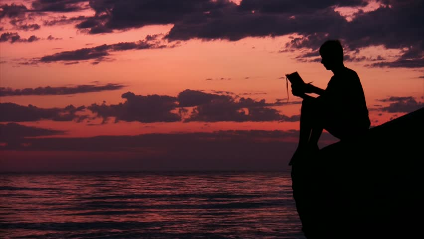silhouette of teenager sits on rock against sunset sky above sea and reads book  - HD stock footage clip