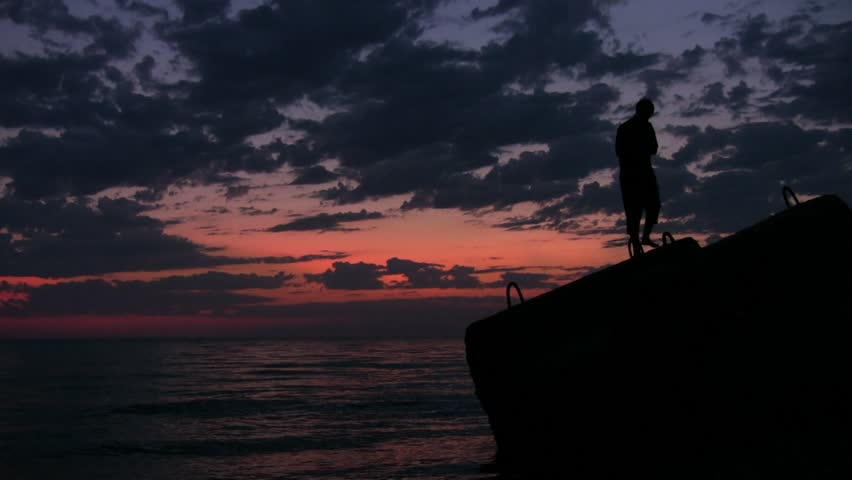 silhouette of young man walks on flagstone above sunset sea  - HD stock footage clip