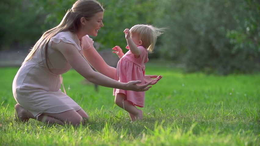 Adorable toddler hardly keeping balance in her first steps to mother