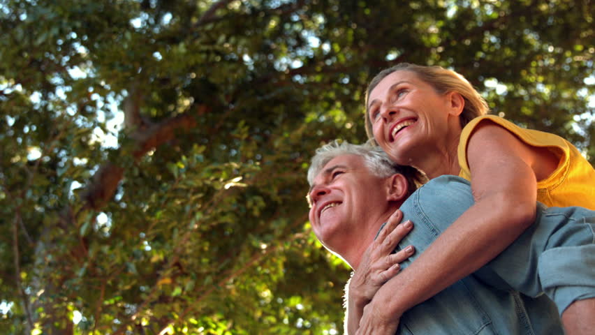 Senior man giving his partner a piggy back on sunny day in slow motion   Shutterstock HD Video #7283827