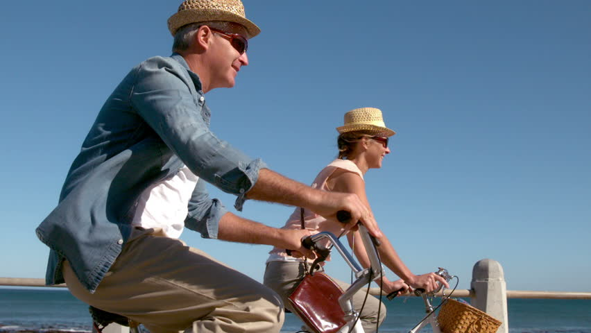 Senior couple going on a bike ride on the pier in slow motion