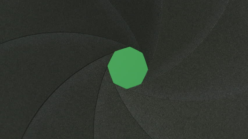 Close-up shot of an aperture or diaphragm blades open and close on green background