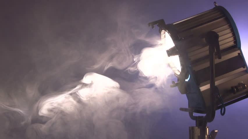 White spot light turns to camera through smokey club