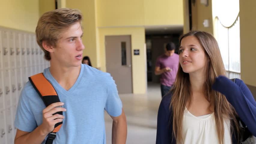 High School Student Couple Walking Along Hallway Stock