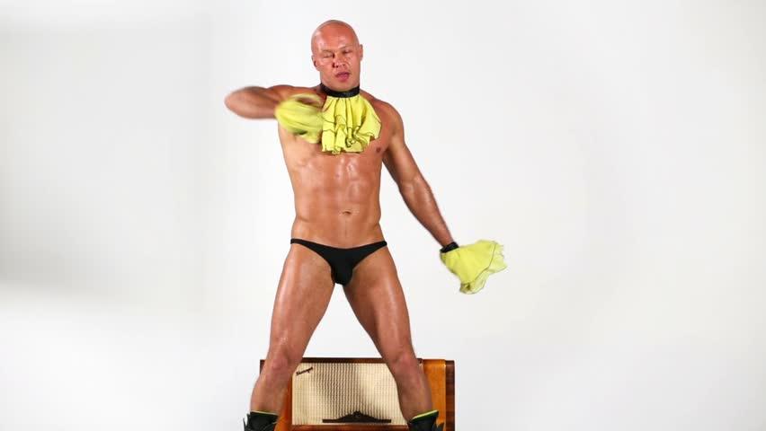 Bald muscular man dances around old radio-gramophone.