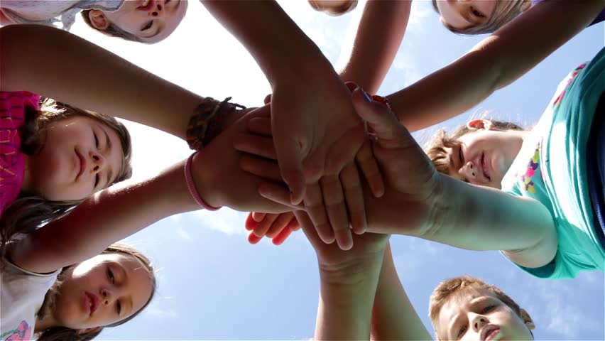 Group of children perform sports greeting with hands on the playground. Young girls and boys perform sports regards with arm. Clouds on the blue sky. Kids playing game. Childhood. Slow motion. 30 fps.