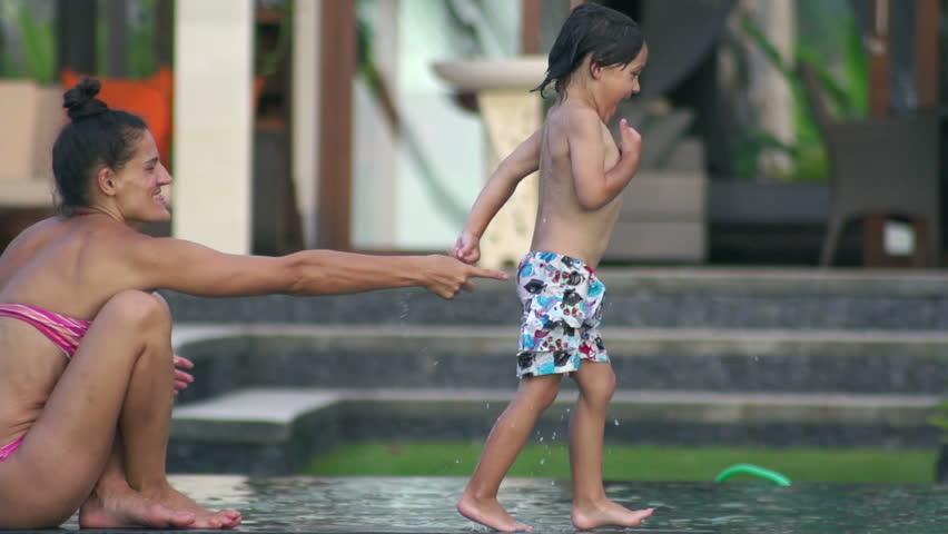 Boy jumping to the pool and diving, slow motion shot  - HD stock video clip