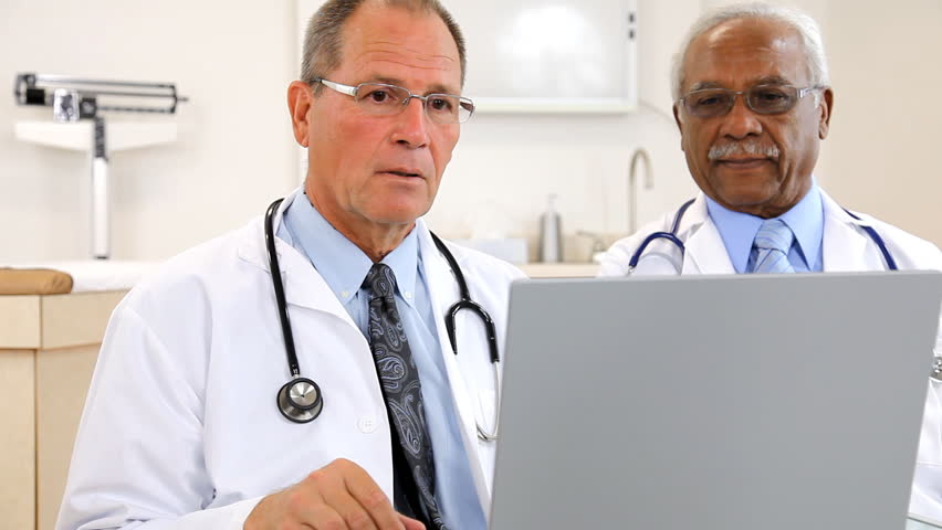 Two doctors reviewing test results on the computer.