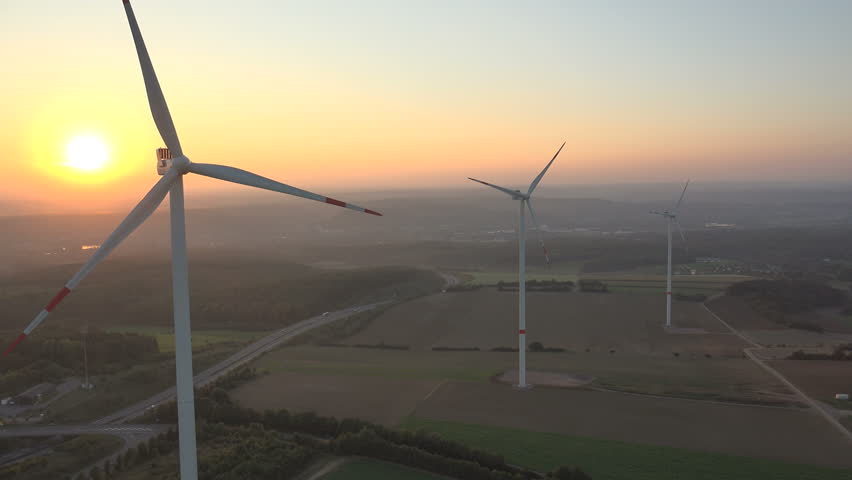 4K. Aerial shot of Power Generating Windmills. Wind turbines producing clean renewable energy. - 4K stock footage clip