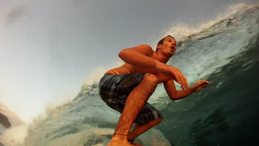 A surfer gets barreled in slow motion, close up