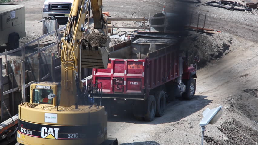 NEW YORK CITY, NY/USA - JULY 20, 2014: A backhoe excavator empties debris into dump truck at a construction site in Queens, New York. Shot through a chain link fence. 1080p HD with natural sound. - HD stock footage clip