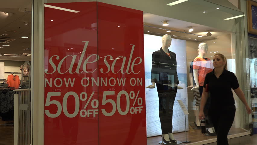 BELFAST, COUNTY ANTRIM/NORTHERN IRELAND - JULY 29, 2014: Department store, unidentified shoppers walk past clothes on half price sale. The financial crisis of 2008 badly damaged the economy.
