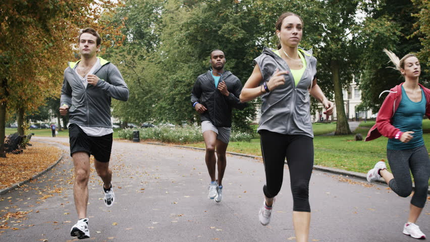 Group of runners running in park wearing wearable technology connected devices